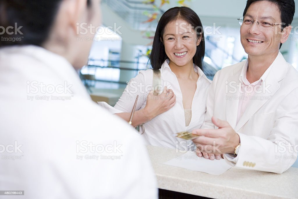 Middle aged husband and wife paying by credit card stock photo
