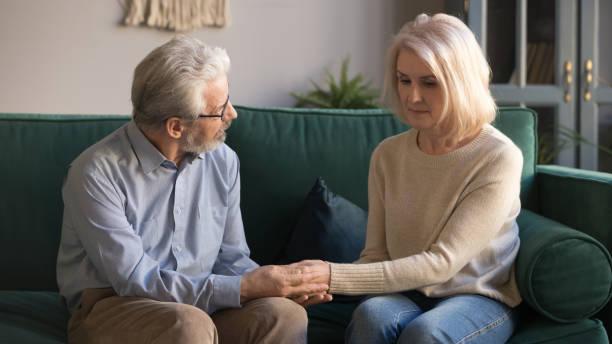 mann mittleren alters, der die hände hält, streichelt verärgerte frau zu hause - sexy granny stock-fotos und bilder