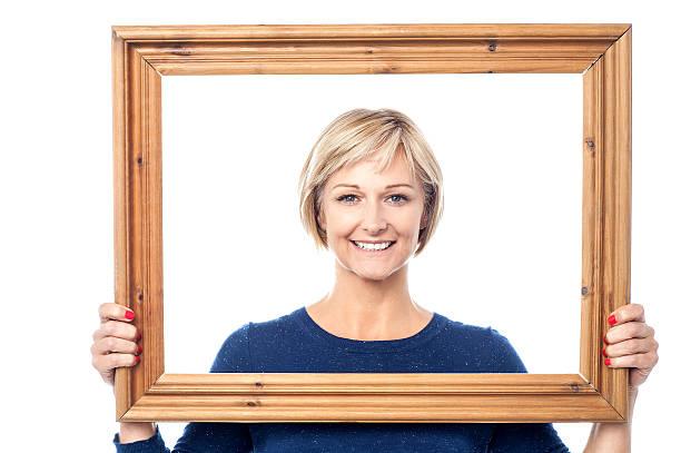 Middle aged lady holding photo frame stock photo