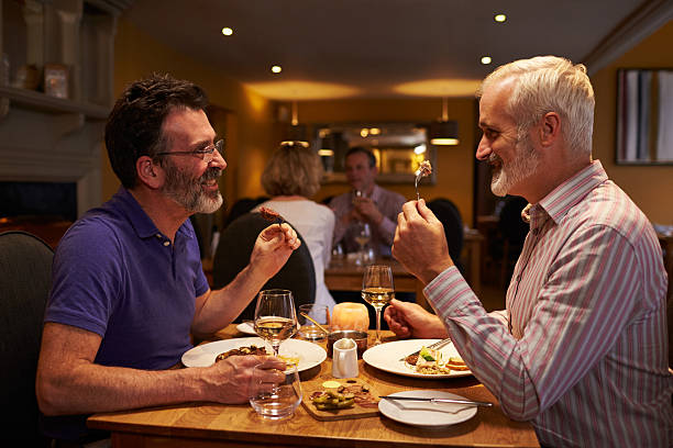 middle aged male couple eating evening meal in a restaurant - middle aged man dating bildbanksfoton och bilder