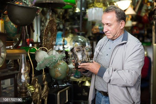 Middle aged man buying retro handicrafts on indoor flea market