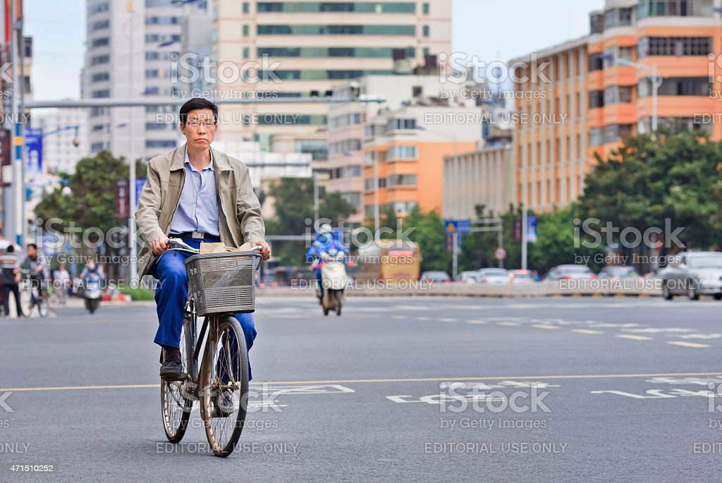 Middle aged man cycles in kunming city center. With a population of...