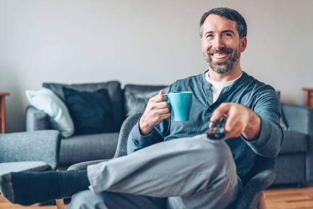 Middle aged man drinking coffee and watching TV stock photo