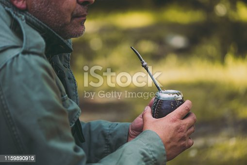 istock Middle aged man drinking yerba mate in nature. Travel and adventure concept. Latin American drink yerba mate 1159890915