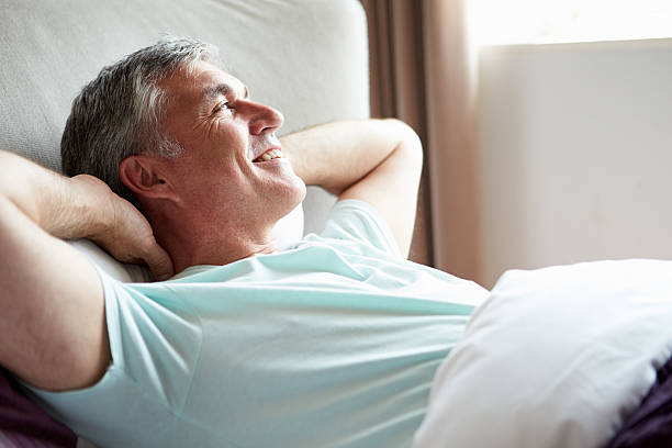 Middle aged man enjoying laying in bed stock photo