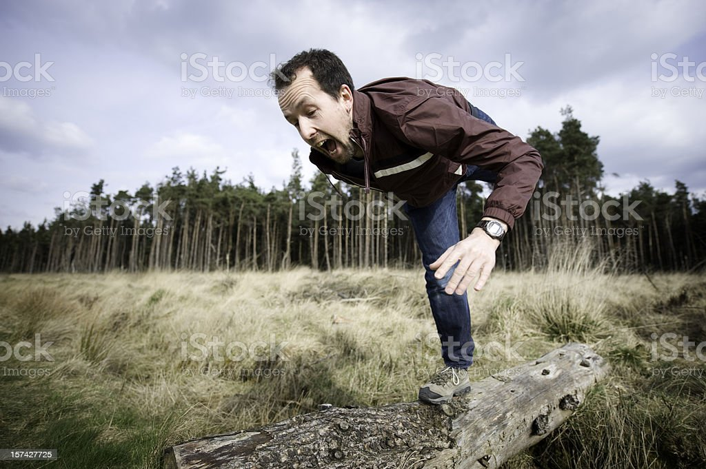 Middle aged man falling off a log stock photo