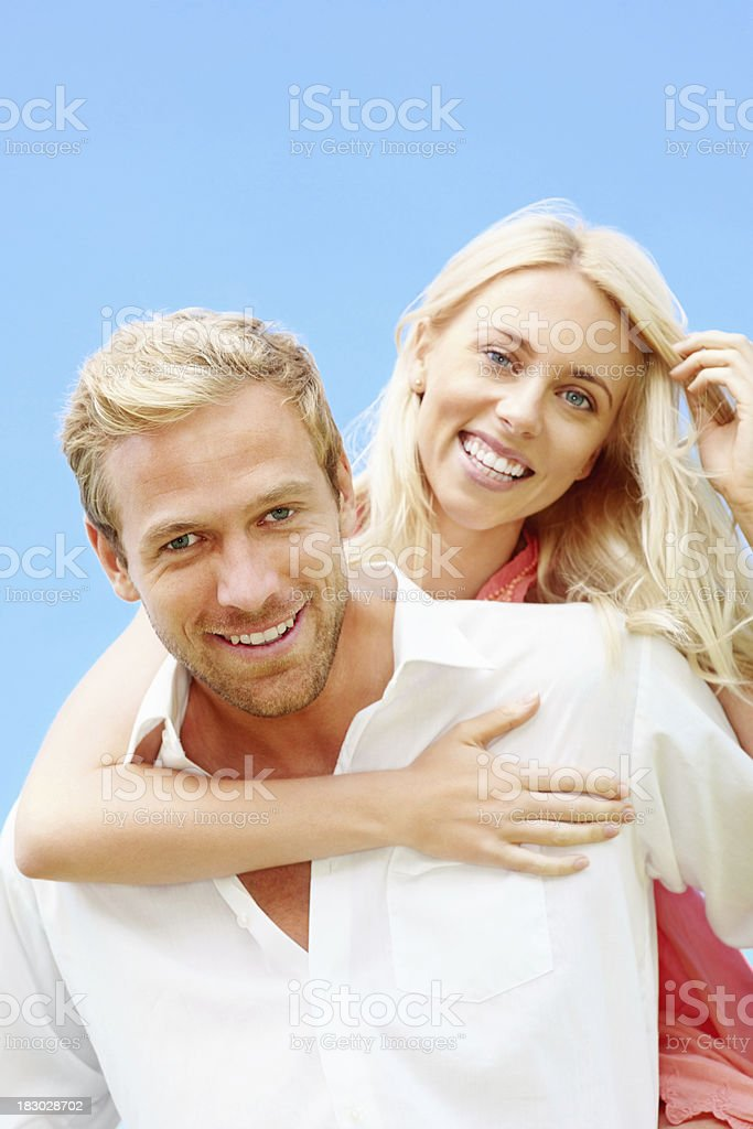 Middle aged man giving woman piggy back ride against sky royalty-free stock photo