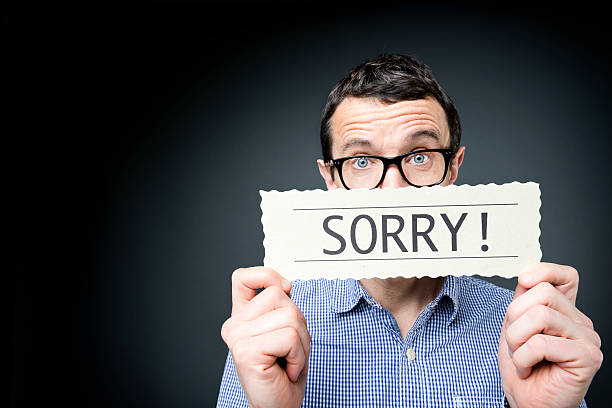 Middle Aged man Holding a Sign Saying Sorry Middle aged man saying sorry. apologist stock pictures, royalty-free photos & images