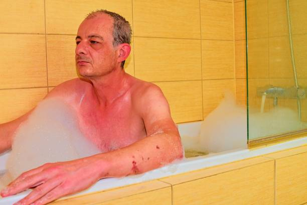 Middle aged man is relaxing in the bath full of foam. Mature man in the bathroom stock photo