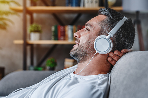 Middle aged man listening music with headphones relaxed in sofa at his home