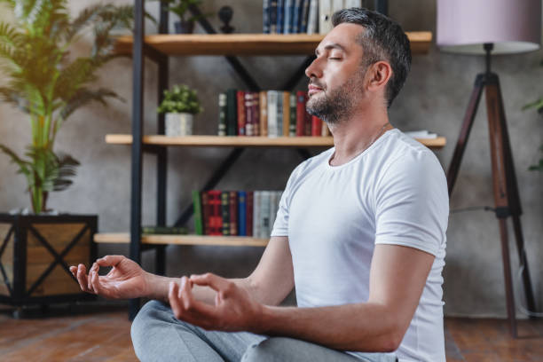 Middle aged man meditating at his living room floor sitting Middle aged man meditating at his living room floor sitting meditating stock pictures, royalty-free photos & images