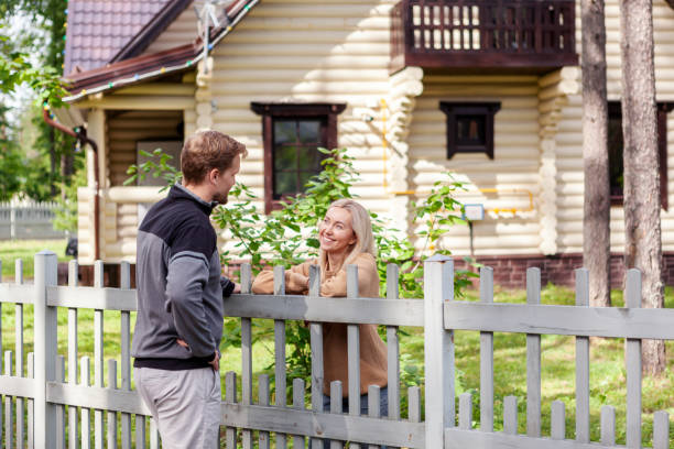 middle aged man meeting smiling female neighbor in countryside and talking cheerfully to her over fence - vizinho imagens e fotografias de stock