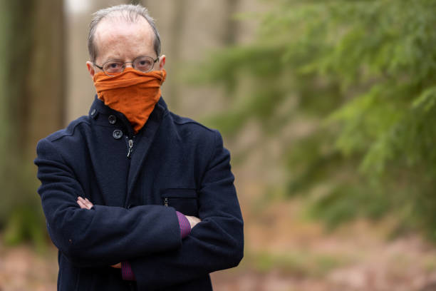 Middle aged man outdoors in the forest, nature, wearing a neck gaiter, bandana type of face protection mask against Coronavirus, COVID-19 stock photo