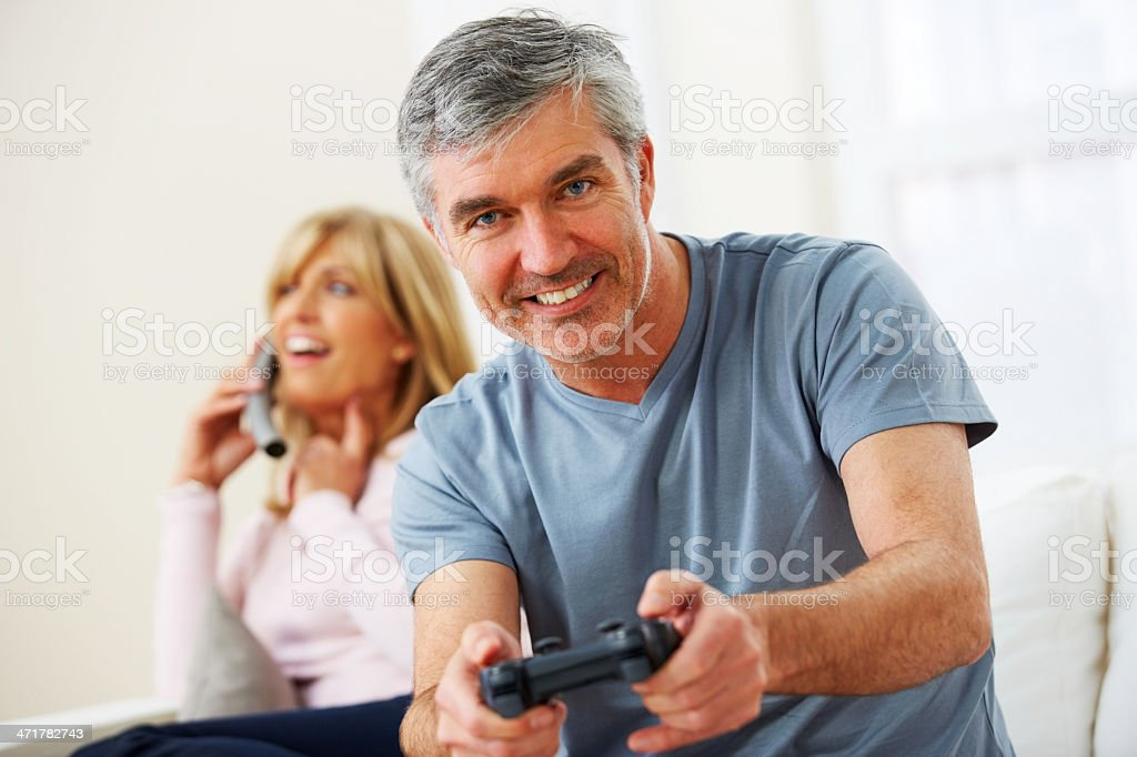 Middle aged man playing video game at home royalty-free stock photo