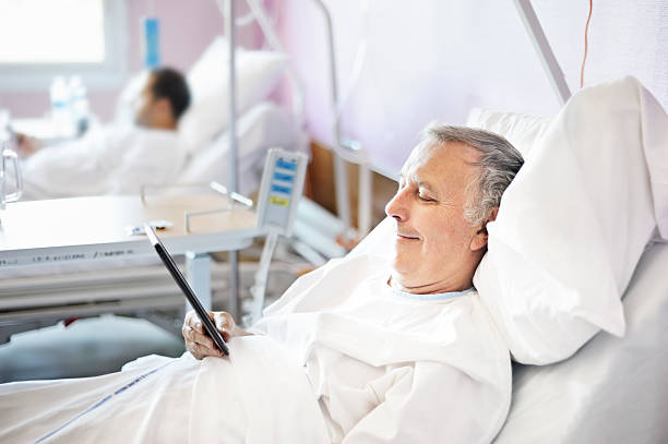 Middle aged man reading a tablet in a hospital bed stock photo