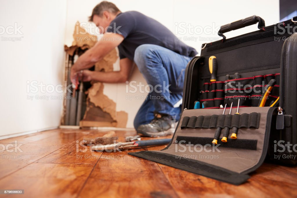 Middle aged man repairing burst pipe,plumbing, focus on foreground stock photo
