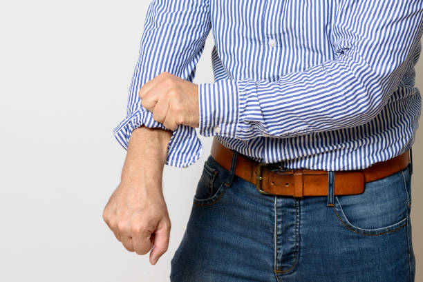 Middle aged man rolling up his sleeves stock photo