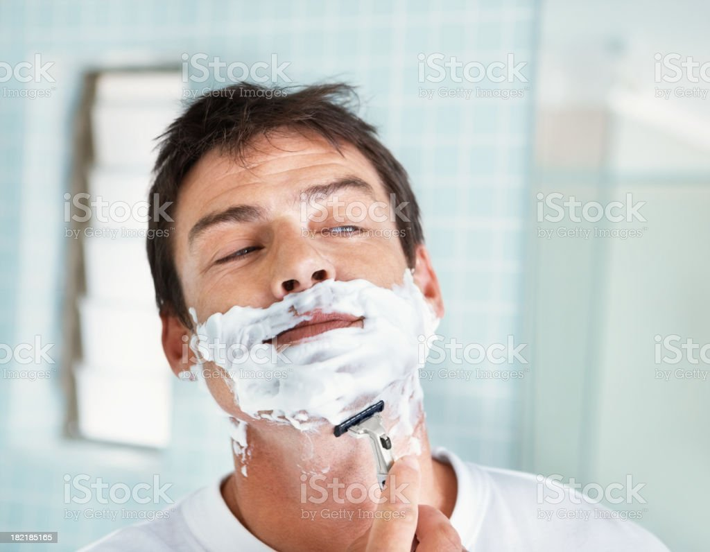 Middle aged man shaving in bathroom royalty-free stock photo