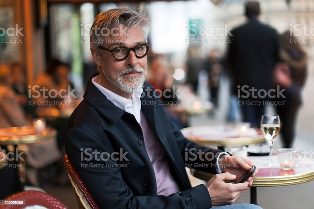 Middle aged man sitting in a french terrace. stock photo