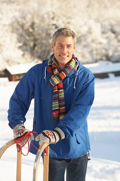 Mittleren Alter Mann stehen In verschneite Landschaft Holding Sledge – Foto