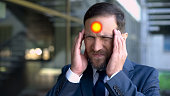 istock Middle aged man suffers from headache, spot indicates migraine pain, closeup 1091529786