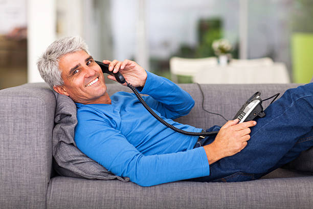 middle aged man talking on the telephone stock photo