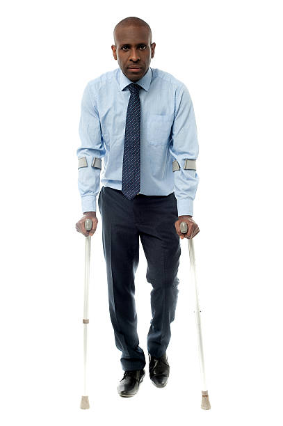 Middle aged man walking with two crutches stock photo