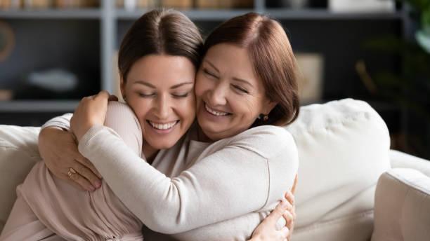 madre de mediana edad abrazando a un niño adulto, sorprendido por las buenas noticias. - hija fotografías e imágenes de stock