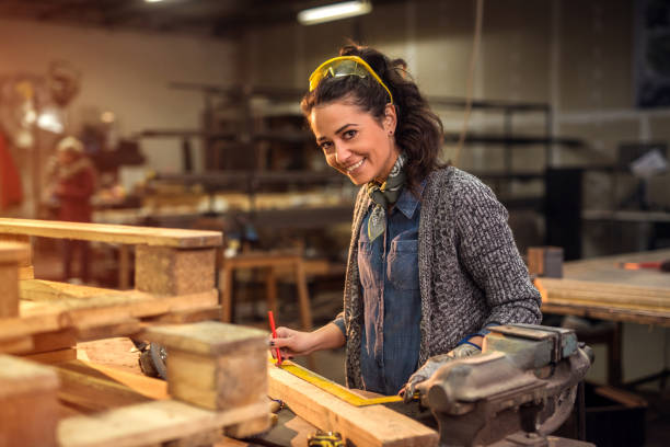 Middle aged professional female carpenter looking at the camera while taking measures of raw wood in her workshop. Middle aged professional female carpenter looking at the camera while taking measures of raw wood in her workshop. carving craft activity stock pictures, royalty-free photos & images