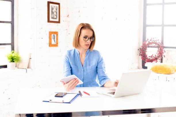 Professionelle Frau mittleren Alters, die digitales Tablet und Notebook verwendet, während sie im Büro arbeitet – Foto