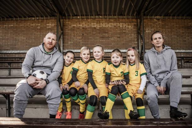 Meio envelhecido ruiva pai e filha loira treinando futebol juntos para um menina de futebol - foto de acervo