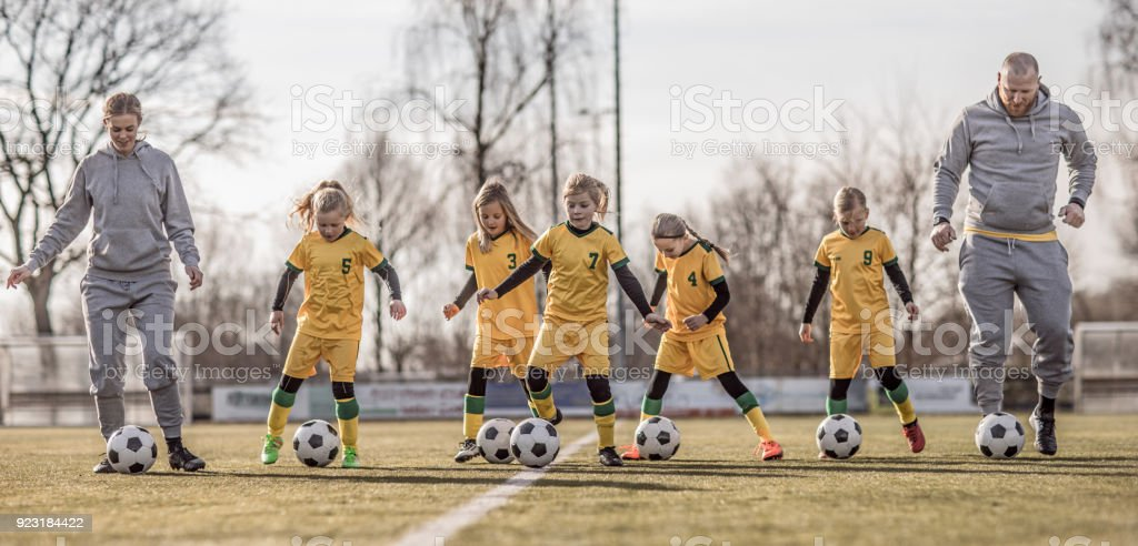 Middle Aged Redhead Father and blonde daughter coaching soccer together to a Girl Football team stock photo