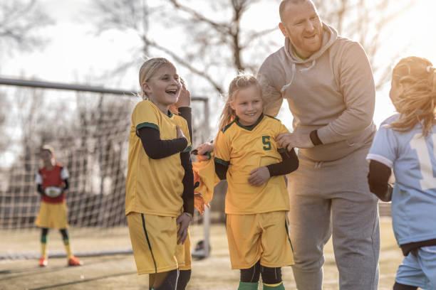 Meio envelhecido pai ruiva, treinador de futebol para um time de futebol de garota no treinamento - foto de acervo