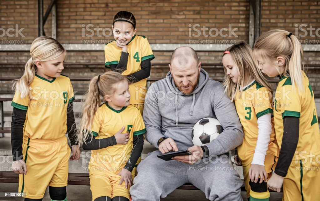 Middle Aged Redhead Father coaching soccer to a Girl Football team at training stock photo