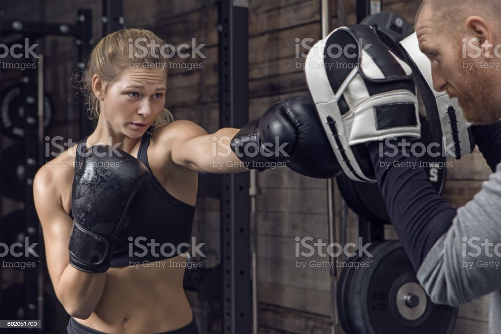 Middle Aged Redhead Handsome Personal Trainer and Beautiful Young Female Athlete in Gym Setting stock photo