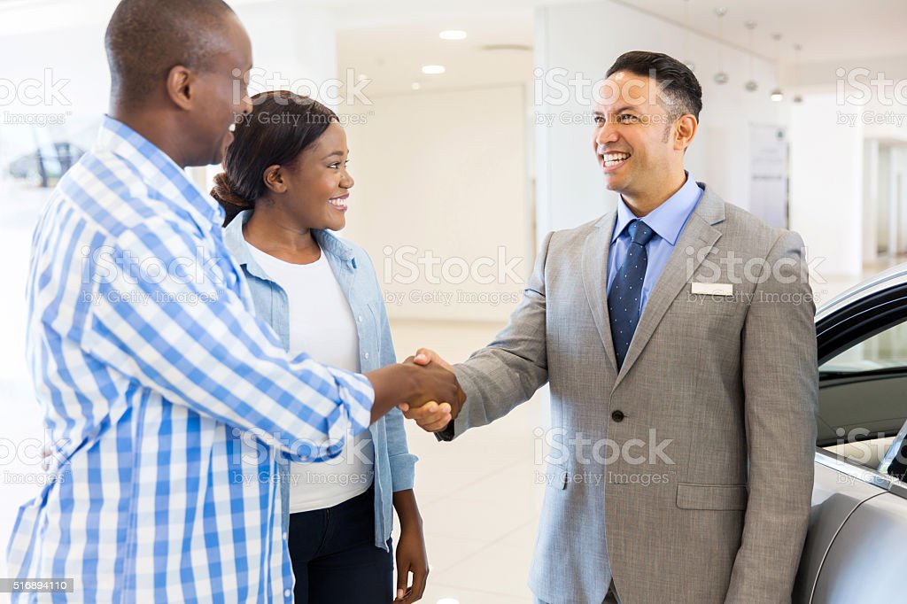 middle aged salesman handshaking with african couple stock photo