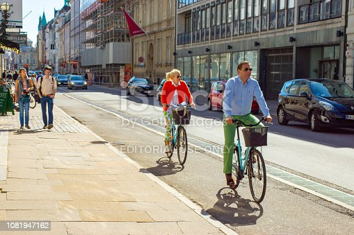 A middle aged smartly dressed couple on bikes, cycling towards the camera in the center of Copenhagen, Denmark.