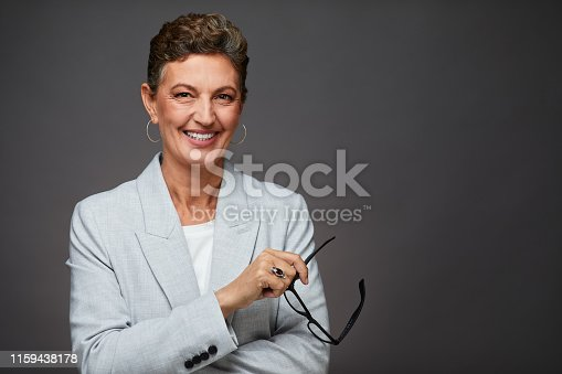istock Middle aged sophisticated businesswoman studio headshot, holding a pair of  glasses. 1159438178