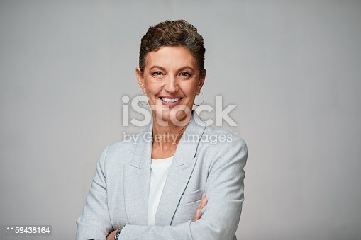 1126471588 istock photo Middle aged sophisticated businesswoman studio headshot, looking at camera and wearing a suit. 1159438164