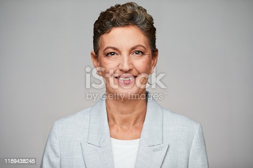1126471588 istock photo Middle aged sophisticated businesswoman studio headshot, wearing a suit. 1159438245