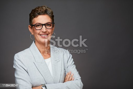 1126471588 istock photo Middle aged sophisticated businesswoman studio headshot, wearing a suit and glasses. 1159438247