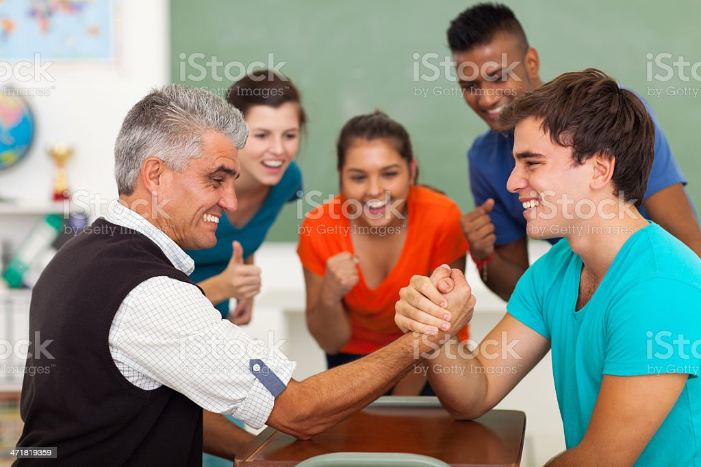middle aged teacher arm wrestling with high school student stock photo