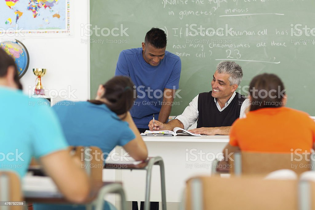 middle aged teacher helping a student royalty-free stock photo