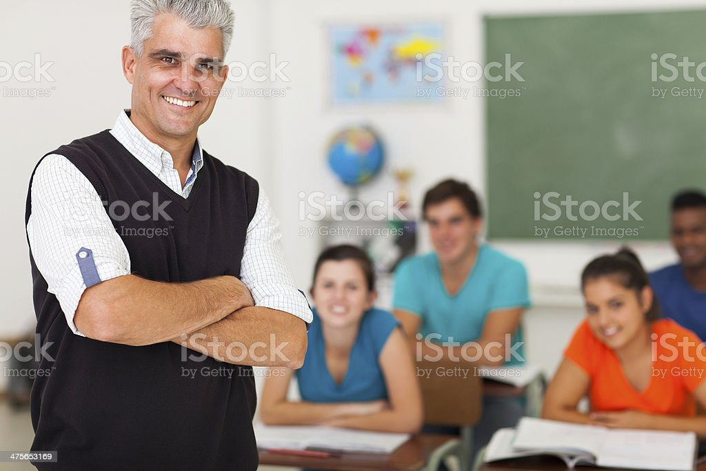 middle aged teacher standing in front of the class stock photo