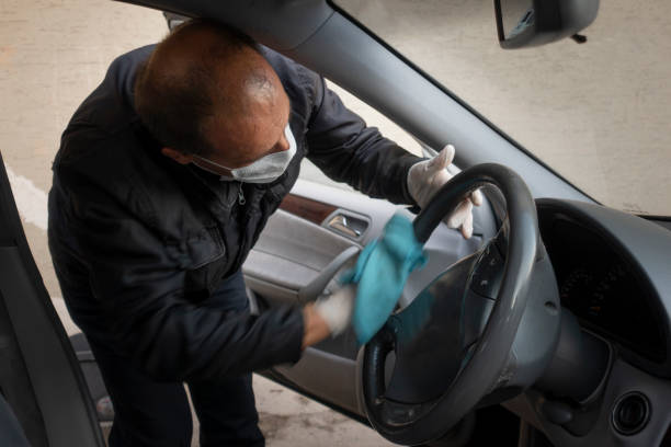 Middle aged Turkish man disinfects his car stock photo