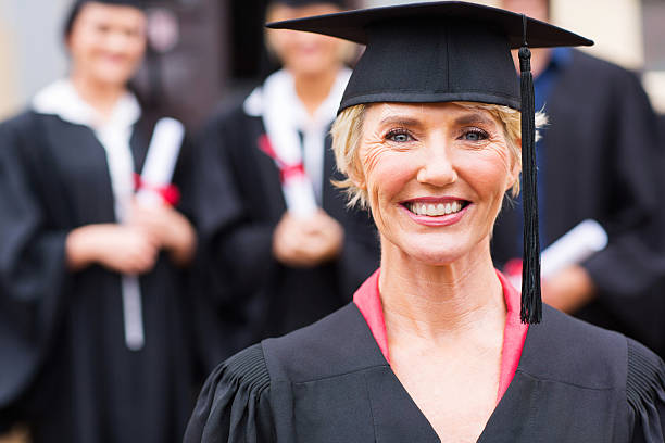 middle aged university professor students graduation ceremony pretty middle aged university professor at students graduation ceremony college dean stock pictures, royalty-free photos & images