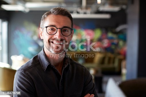 Middle aged white male creative in casual office lounge area looks to camera smiling, close up