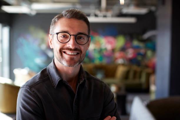 w średnim wieku biały mężczyzna kreatywny w swobodnym salonie biurowym wygląda na kamerę uśmiechniętą, z bliska - selektywna głębia ostrości zdjęcia i obrazy z banku zdjęć