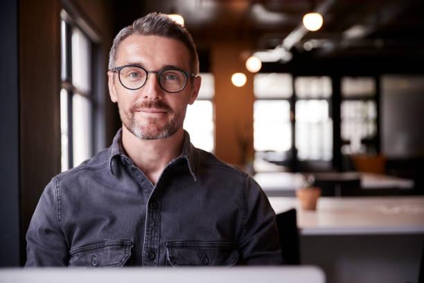 w średnim wieku biały mężczyzna kreatywny siedzi w biurze uśmiechając się do kamery, głowy i ramion, z bliska - selektywna głębia ostrości zdjęcia i obrazy z banku zdjęć