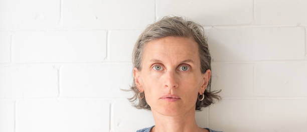 Middle aged woman against white painted brick wall stock photo
